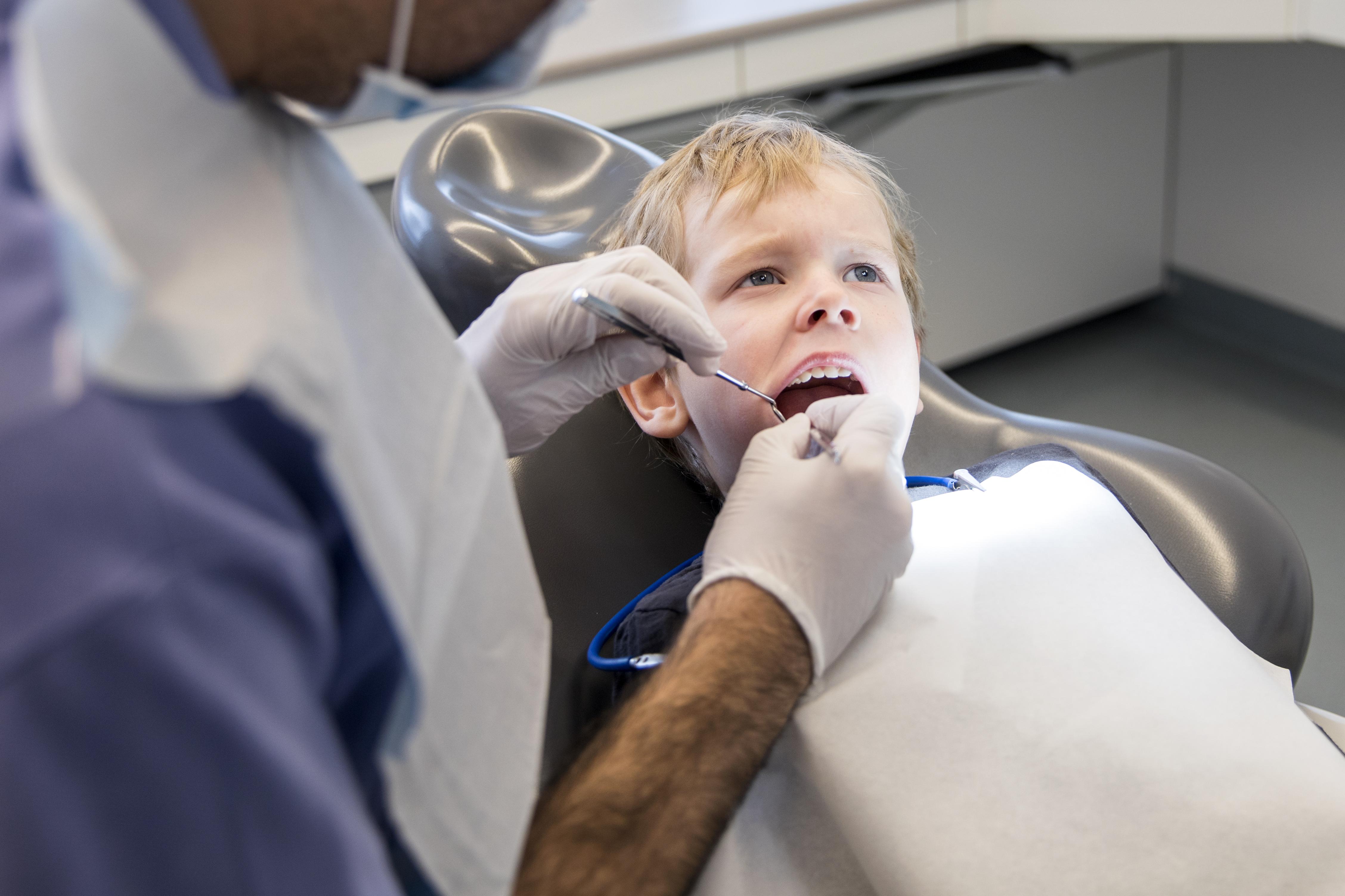 Ett barn i en tandläkarstol som blir undersökt i munnen.