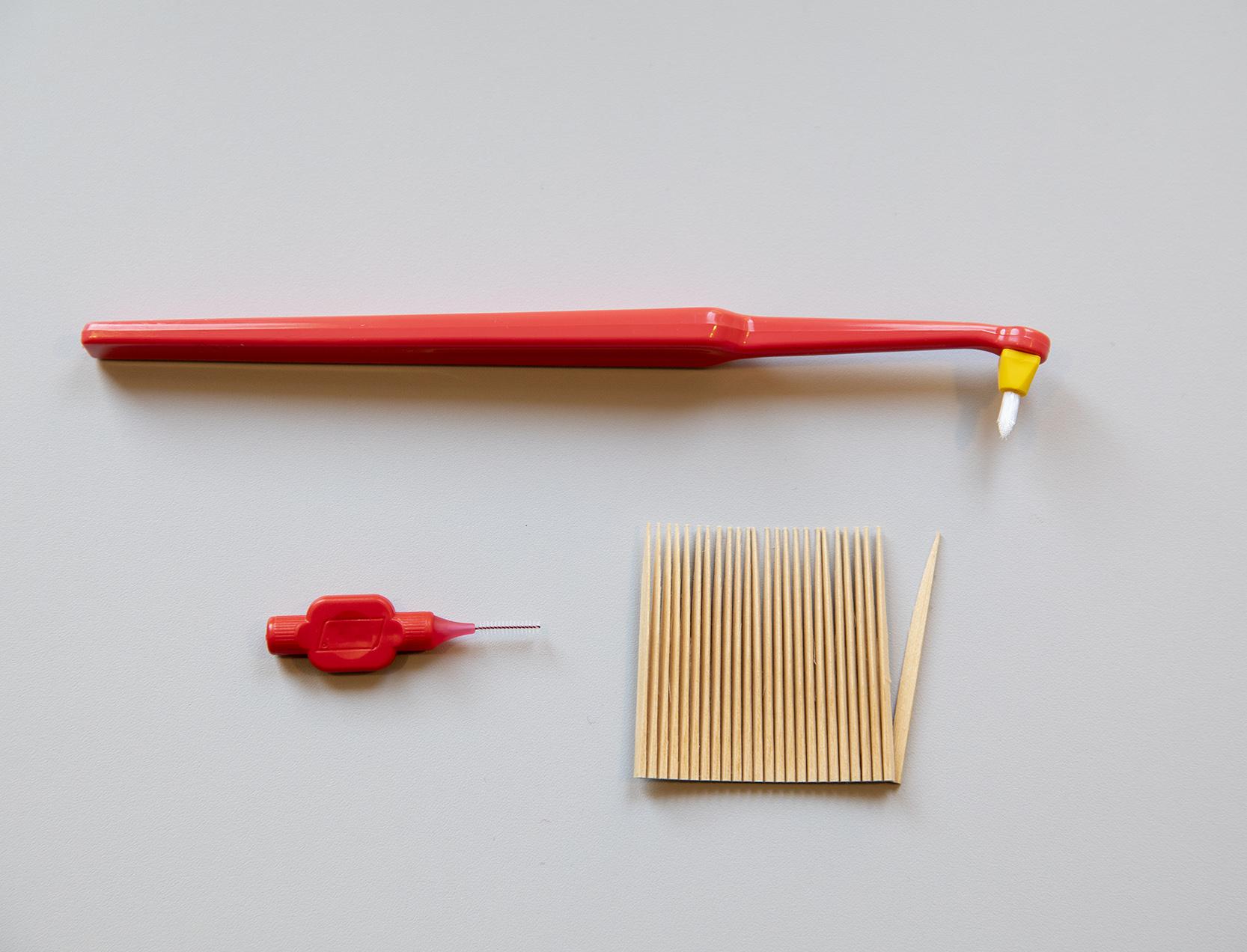 Vinkelborste, en mellanrumsborste och tandstickor. Fotografi