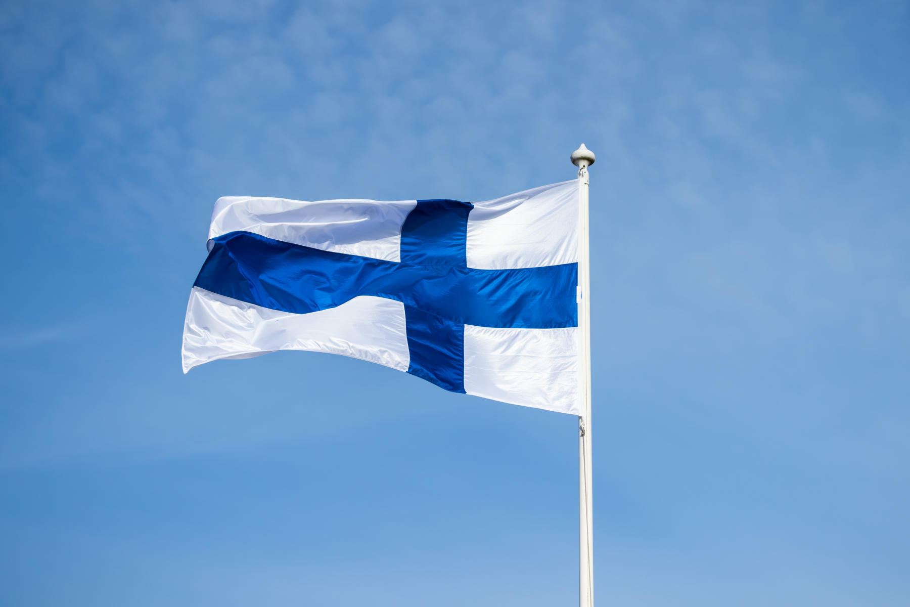 Finska flaggan vajande i vinden- finnish national flag on the wind against the blue sky