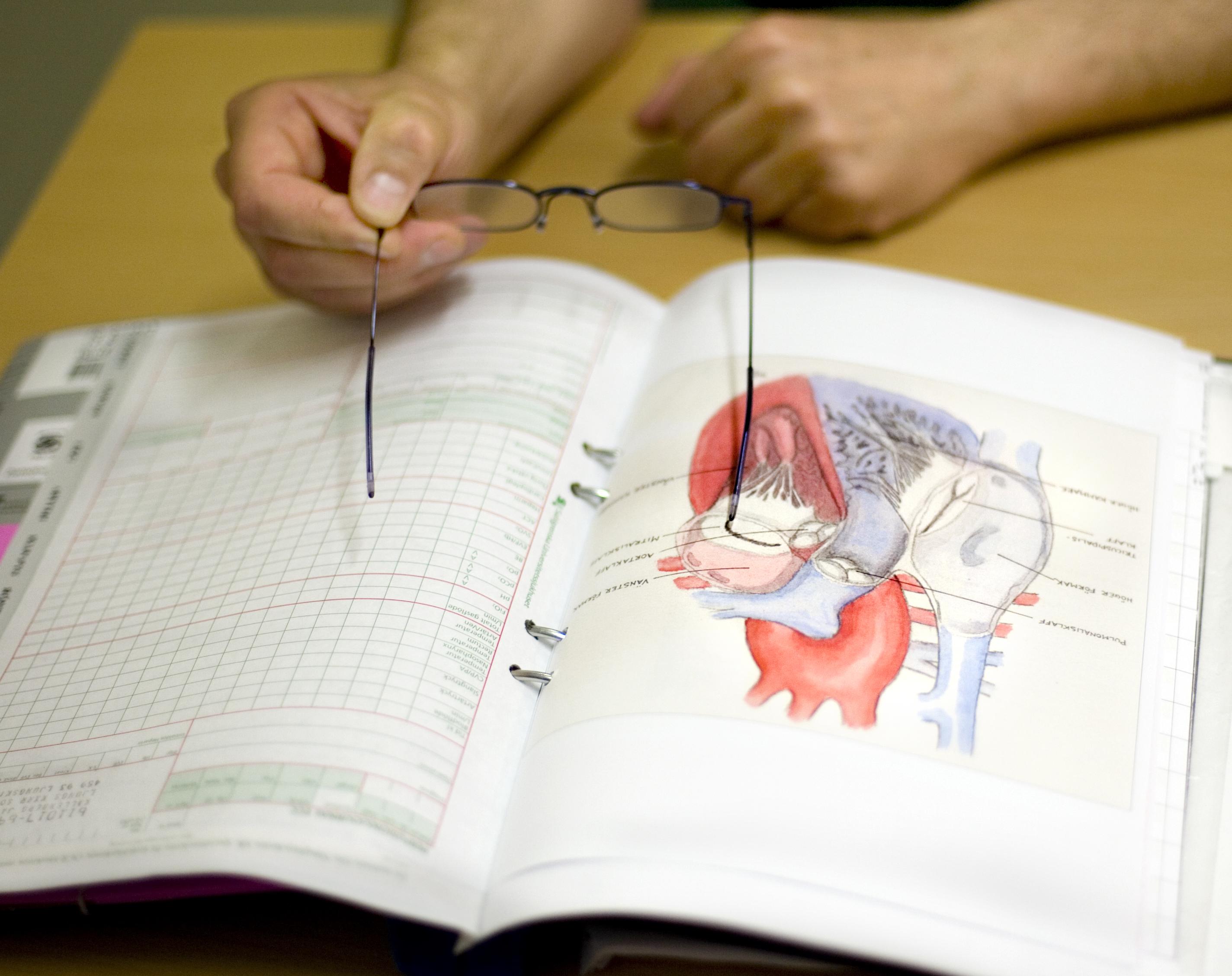 Kirurg visar på hjärtskiss hur operation ska gå till
